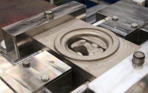 Das Werkzeug verfügt über seitliche Stempel. Wenn sich das Gesenk schließt, fahren sie aus und erzeugen die Vorbohrung für den Kolbenbolzen.